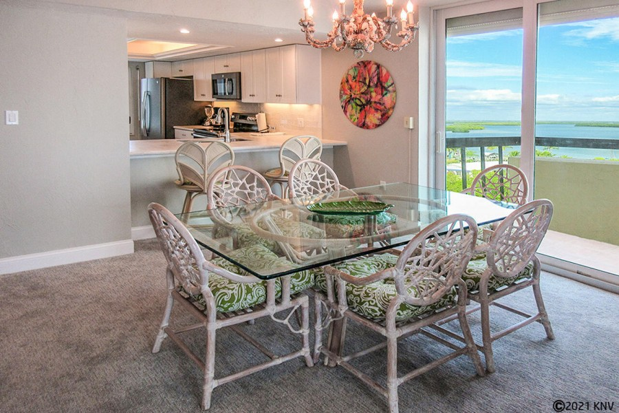 Glass topped dining table features a balcony view of the Bay