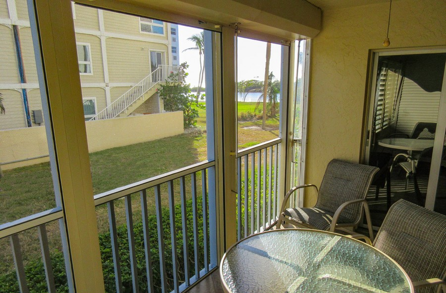 Sand Caper 108 Screened In Lanai with comfortable furniture, view of the grounds and a partial view