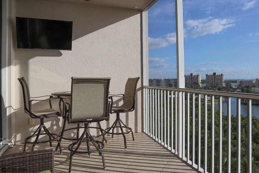Screened In Lanai features a TV, Dining Table and Chairs and comfortable lounge chairs