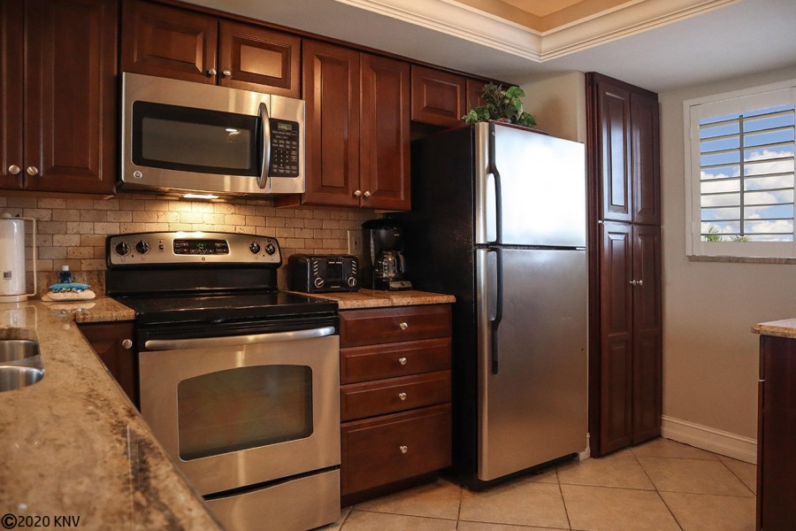There is a washer and dryer tucked away beside the full capacity refrigerator.