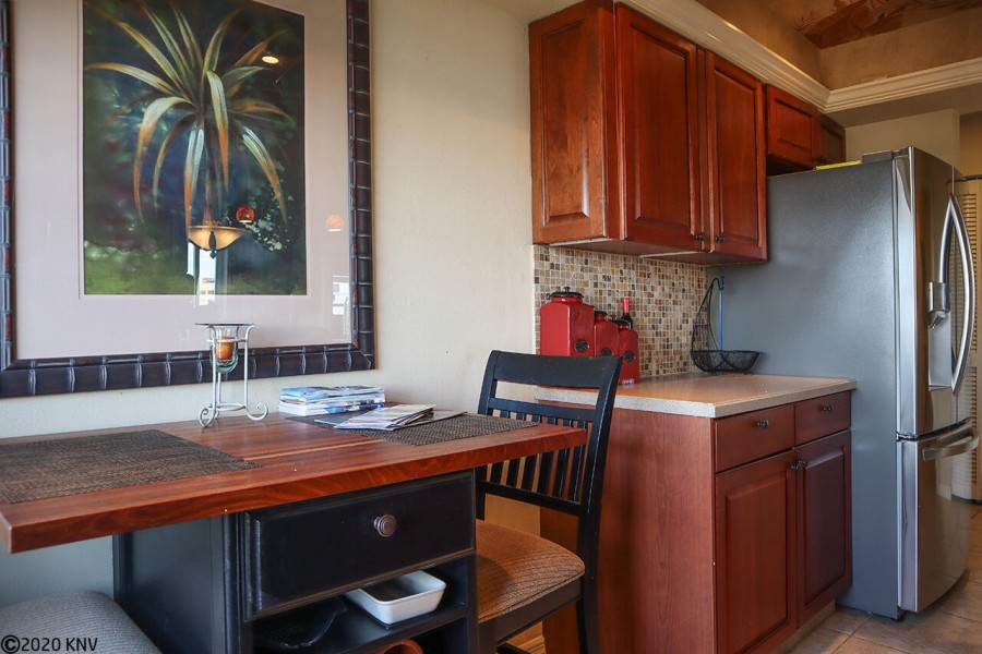 The fully equipped kitchen boasts custom cabinets, gleaming countertops, a wine rack and table for 2