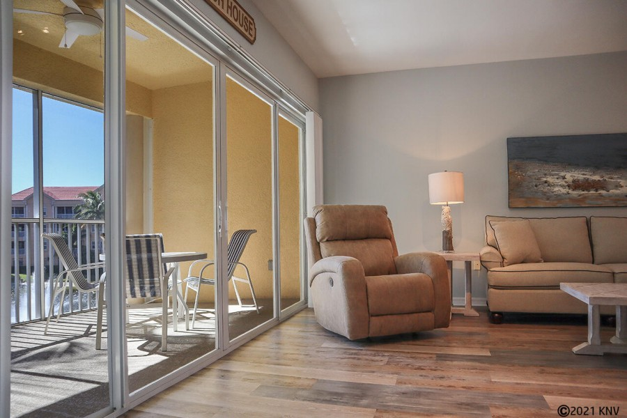 Open concept living area features floor to ceiling glass sliders.