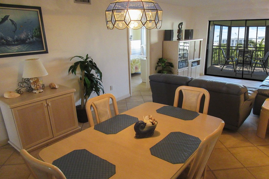 Harbour Pointe 524N - Living and Dining Area leads to Screened In Lanai with beautiful Bay and Canal